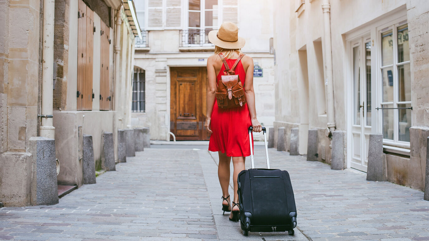 woman in red dress and straw hat with suitcase walking down an empty Spanish street in the afternoon
