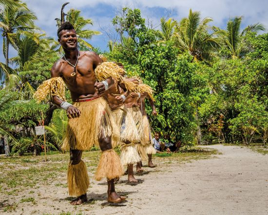 Locals in Vanuatu in traditional dress line up to greet arriving cruise guests