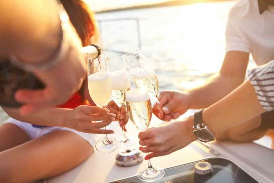 Friends cheering-glasses-on-yacht-with-champagne