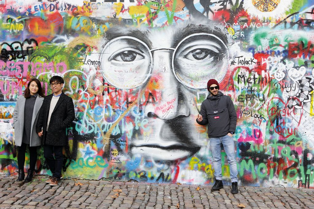 Tourists pose by the John Lennon graffiti wall in Prague city