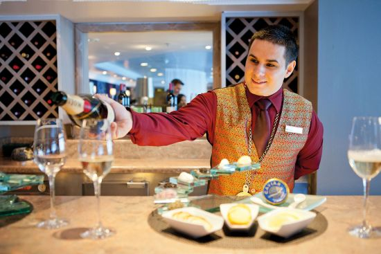 Waiter pouring wine on a cruise as part of a drinks package deal