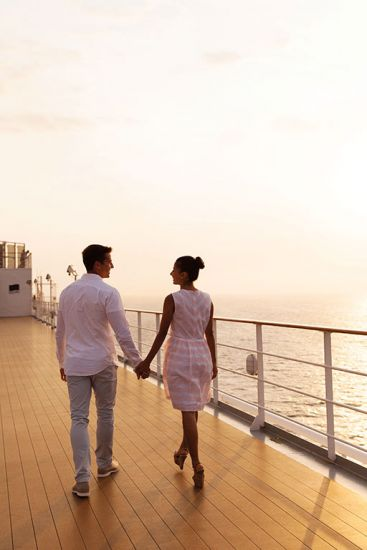 Coupling walking hand in hand on a ship deck on a cruise