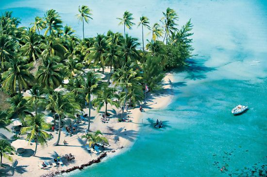 Ariel view of Motu Mahana island, owned by Paul Gauguin cruises, with sea, sand and palm trees