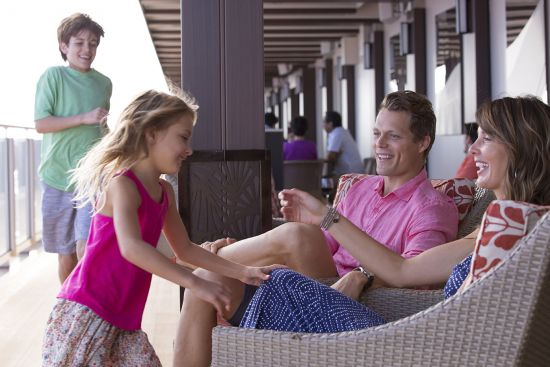 Parents and daughter and sun smiling on ship deck on a family cruise