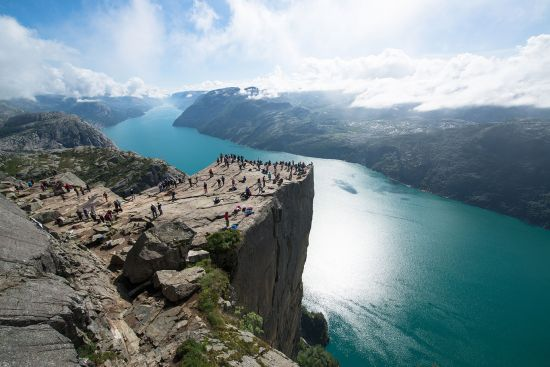 people standing on Cliff Preikestolen in fjord Lysefjord - Norway