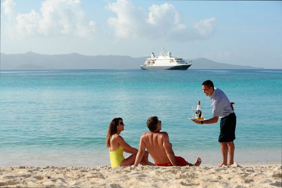 Waiter on a beach offering drinks to cruise passengers in the Caribbean