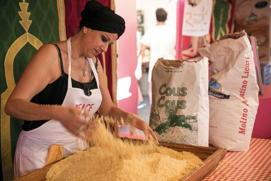 Woman preparing cous cous at the food festival in Sicily