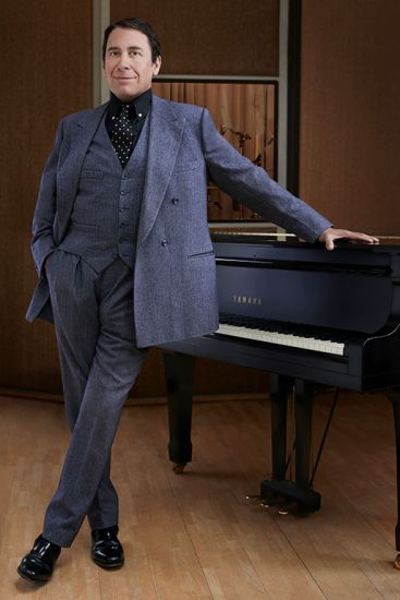 Jools Holland standing by the piano, celebrity interview