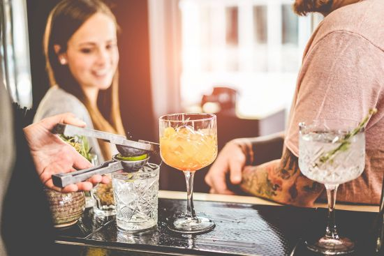 Solo travel: female making friends on cruise as bartender makes drinks