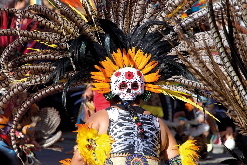 Man dressed in skull costume and feathers at Mexico festival