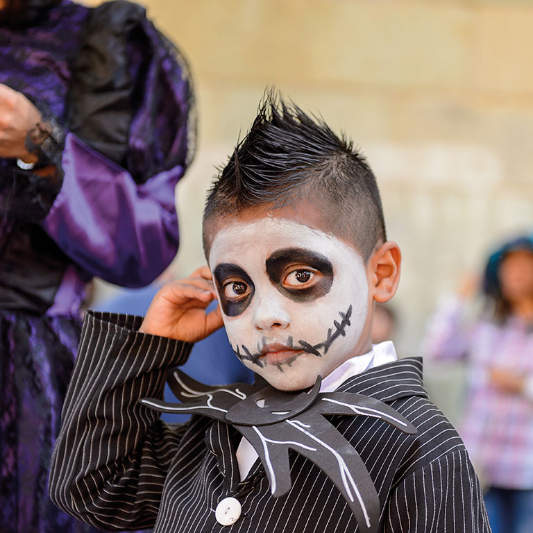 Boy dressed up with skeleton mask at Mexico festival